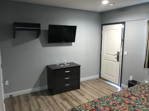 Empire Inn LAX - Wall-Mounted Flat Screen TVs with Clothes Rack in Rooms